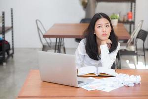 retrato mujer joven asiática que trabaja en línea en la computadora portátil. foto