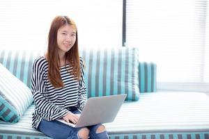 mujer asiática joven que usa la computadora portátil para el ocio en el sofá en la sala de estar. foto