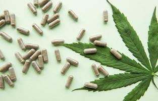 CBD pills. Group of clear CBD Cannabidiol capsules and hemp leaf photo