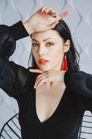 mujer vistiendo un vestido negro, aretes rojos en estudio de luz foto