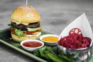 Modern fusion beef burger set with lotus chips ketchup and spicy chili sauces photo