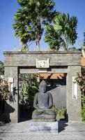 Estatua de Buda de piedra tradicional balinés y puerta en Bali, Indonesia foto