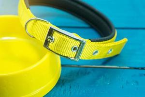 Pet collars and Bowls of yellow on wooden background. photo