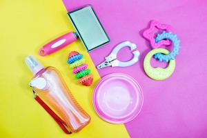 Pet accessories concept - bowl, toys, brush, collars, and nail scissors on yellow and pink background. photo