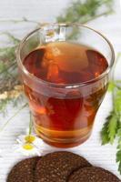 té con galletas y manzanilla. una taza de té caliente y un montón foto