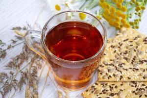 té con galletas. taza de vidrio con té caliente, galletas y flores silvestres. foto