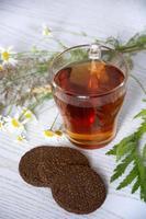 té con galletas y manzanilla. taza de vidrio con agua caliente foto