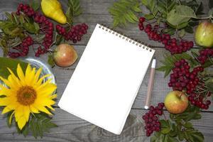 Bloc de notas con una hoja de papel en blanco. Rowan sobre un fondo de madera foto
