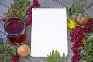 Bloc de notas con hoja en blanco en blanco para texto. taza de té foto