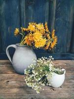 Beautiful field flowers in cup and ceramic jug on wooden backdrop photo