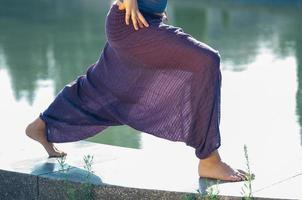 Atractiva mujer en pantalones morados practicando asanas de yoga al aire libre foto