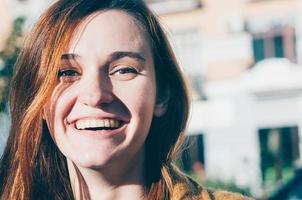 mujer joven morena pecosa sonriendo foto