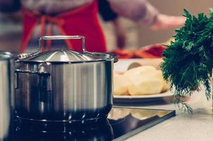 Cooking pot and vegetables, healthy ingredients for soup or stew on table, woman standing in the kitchen in the background. Homemade food, cooking, vegetarian concept photo