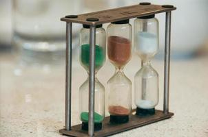 Selective focus closeup image of sandglass showing when three different types of tea including white, green, and black are ready. Stylish metal frame. Blurred light background photo