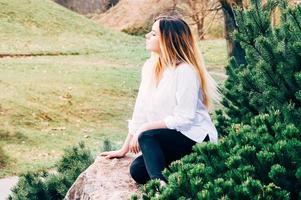 Un retrato de una joven y bonita chica de pelo largo con camisa blanca, sentada sobre una piedra en un parque, con fondo de hierba verde y pinos en primer plano foto