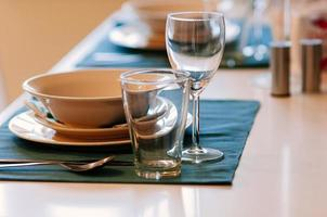 Close up dining setup with empty wine and water glasses, silver cutlery and blue napkins, decorations and items served for food, arranged by catering service in a modern restaurant, cafe photo