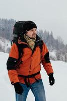 Tourist man walking through snow on winter day, mountain forest landscape. Blue jeans, orange garment, red backpack. Hiking travel extreme concept. Selective focus photo
