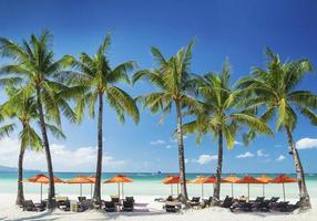 Beach lounge bar loungers chairs and umbrellas on tropical exotic Boracay island in Philippines photo