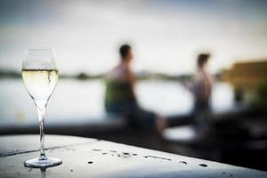 Glass of sparking champagne wine at modern outdoor bar at sunset photo