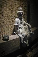 Escultura de estatua de piedra blanca tradicional china en exhibición bajo una luz cambiante dramática en xiamen china foto