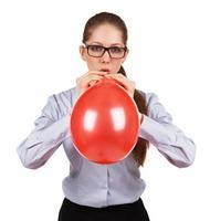 Stylish girl inflates a big red ball photo