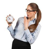 mujer sorprendida sosteniendo un reloj despertador en una mano foto