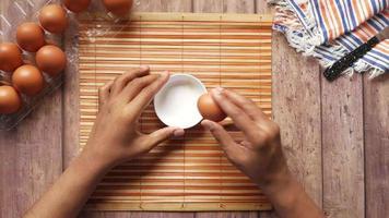 homem quebrando ovo e despejando em um pequeno recipiente na mesa, video