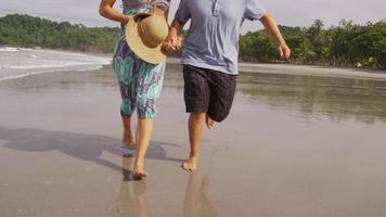 coppia in esecuzione sulla spiaggia, primo piano dei piedi, rallentatore. video