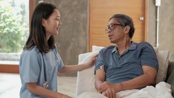 Doctora comprobando la salud del paciente masculino anciano asiático en casa video