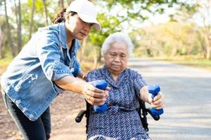 Asian senior or elderly old lady woman exercise with dumbbell in park. photo