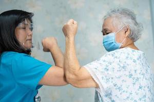 Asian doctor and elder patient bump elbows to social distancing photo