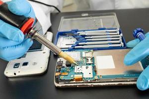 técnico que repara el interior del teléfono móvil con un soldador. foto