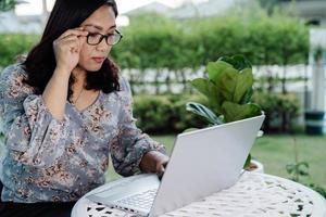 mujer de negocios asiática trabajar desde casa en la computadora portátil, quedarse en casa. foto