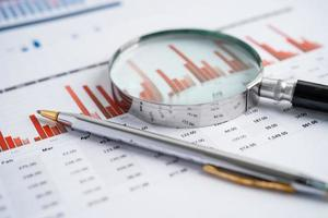 Magnifying glass on charts graphs paper. Financial development photo