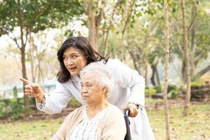 Doctor help Asian senior woman patient sitting on wheelchair photo