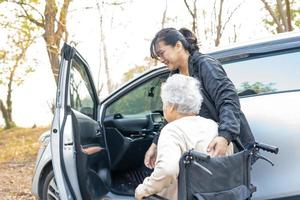 Help and support asian senior woman patient  get to her car, photo