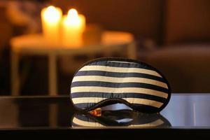 Stylish sleeping mask on table in dark room photo