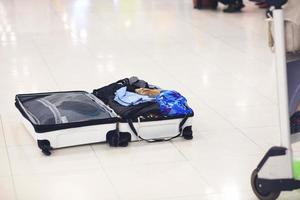 Open suitcase to inspection at air port, travel preparation photo