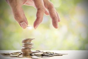 Mano humana colocando una moneda sobre un montón de monedas sobre un fondo hermoso. foto