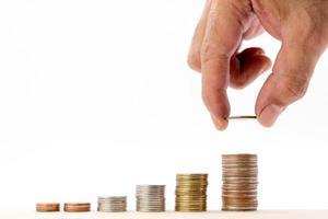 Mano humana poniendo una moneda en un montón de monedas sobre fondo blanco. foto