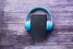 Audio book concept. Headphones and notepad on wooden background photo