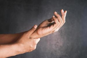 Man suffering pain in hand against black background photo