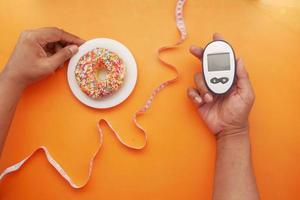 Mantenga a mano herramientas de medición para diabéticos y donas en naranja foto