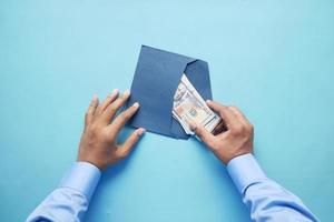 Person hand putting cash in a envelope, top view photo