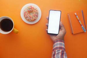 Mano de hombre joven con teléfono inteligente con té y galletas en la mesa foto