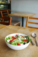 Greek salad in a bowl on cafe table with copy space photo