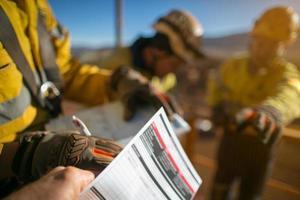 Trabajadores de la construcción que firman el permiso de trabajo de alto riesgo en alturas foto