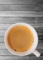 Taza de café caliente con trazado de recorte vista superior sobre fondo de tablones de madera foto