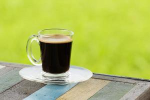 hot black coffee on wooden table with green nature background photo
