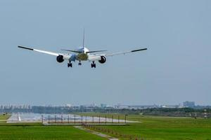 Commercial airplane landing on runway in airport photo